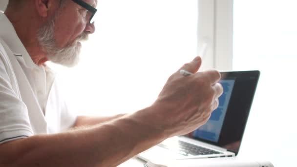 Ältere Mann mit Laptop zu Hause arbeiten. Alter Mann mit Computer zu Hause auf Stuhl sitzend und mit Blick auf den Bildschirm. Ältere Großvater tragen Brillen und arbeiten am Laptop im Wohnzimmer