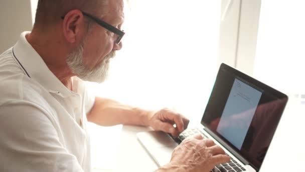 Älterer Mann, der zu Hause mit einem Laptop arbeitet. Schriftsteller oder Wissenschaftler bei der Arbeit. Seniorin schreibt Brief am Computer, Fernarbeit, Freiberufler