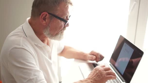 Writer or scientist at work. A senior citizen writes a letter using a computer, remote employment. A mature man uses a laptop to work at home. Shutdown, closes laptop cover