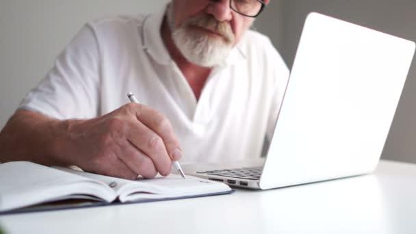 Geschäftsmann mit grauem Bart arbeitet im Büro mit Laptop. macht sich Notizen mit dem Bleistift in einem Notizbuch. Fernbeschäftigung, Rentner bei der Arbeit, Mann am Computer