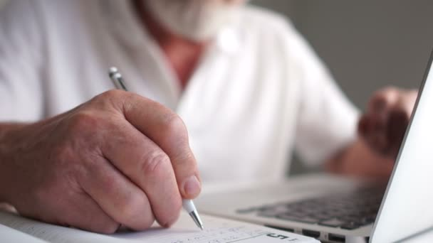 Close-up, an elderly man makes notes with a pen in a notebook while working with a laptop. Mature businessman working at home retiring coworking