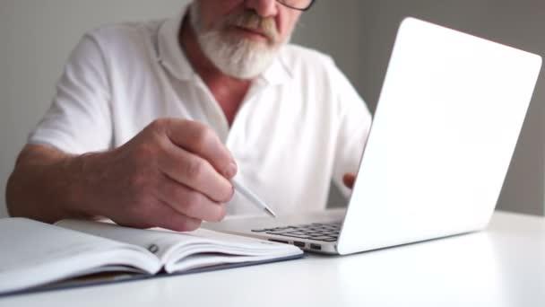 Ein älterer Mann in weißem T-Shirt und grauem Bart macht sich mit einem Stift Notizen in einem Notizbuch, während er mit einem Laptop im Internet arbeitet. Büroangestellte, Abteilungsleiterin, Geschäftsfrau