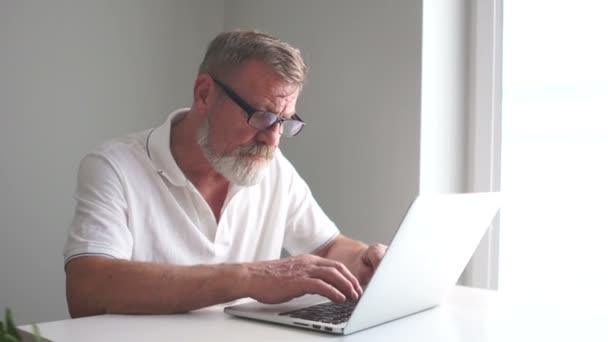 Der müde ältere Geschäftsmann arbeitet im Büro mit einem Laptop. nimmt der Mann seine Brille ab und wischt sich die Augen. Wochentage, Rentner und Computer
