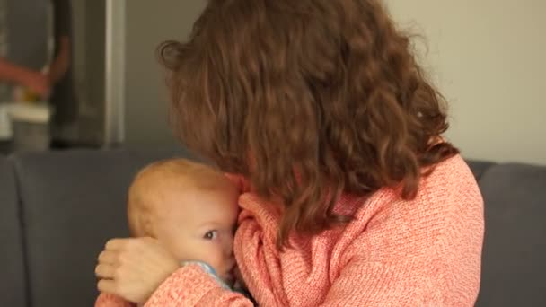 Beautiful curly mother breastfeeds her one and a half year old baby. Indoor portrait. Mothers Day