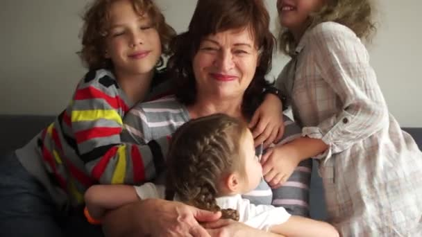 Grandmother posing with grandchildren. Two girls and one boy. Happy children hug their grandmother, portrait of Indoor. Two generations, a large family, a grandmother and grandchildren