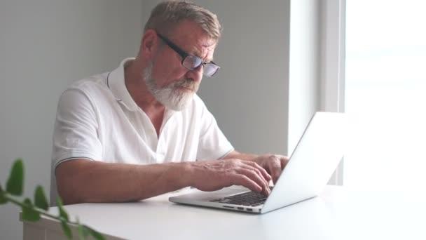 Geschäftsmann mit Laptop im Büro. Abteilungsleiter, reifer Mann mit Bart und Brille arbeitet mit Laptop