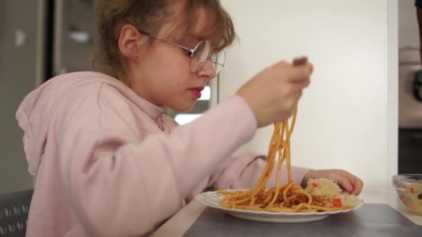 Teenager-Mädchen essen Spaghetti Bolognese in einer Schulmensa. Gesunde Ernährung Mädchen trägt Brille