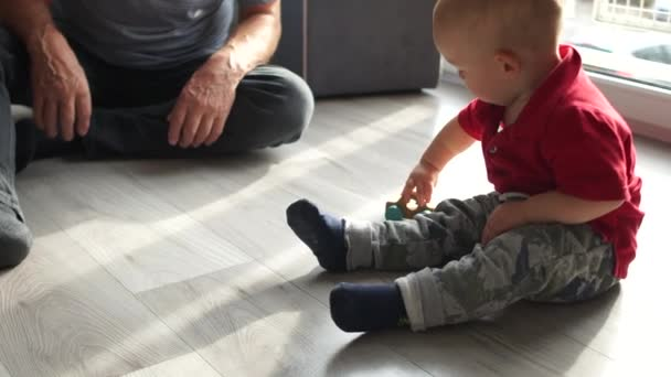 Toddler and an elderly man are playing with a wooden toy car on the floor. Happy family, grandfather and grandson