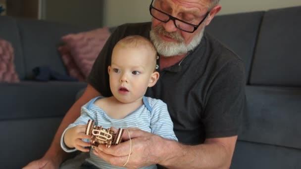 Der glückliche Opa sitzt auf der Couch und genießt die Zeit mit dem Enkel im Vorschulalter zu Hause. Opa und Enkel spielen mit Holzspielzeug, umarmen sich und lächeln, während sie sich zu Hause ausruhen