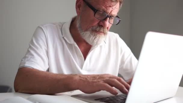 Opa mit Brille und grauem Bart beschäftigt sich in der Nähe des Laptops, starrt auf den Bildschirm und tippt. Reifer Mann und Computer