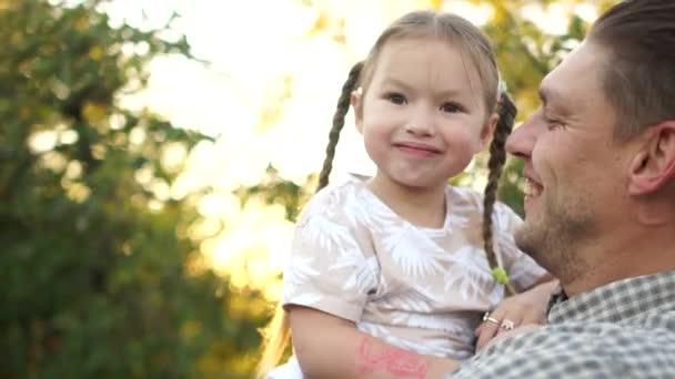 ein schönes fünfjähriges Mädchen mit Zöpfen im Arm lacht und prahlt in der Ferne. Vater und Tochter spazieren in der untergehenden Sonne