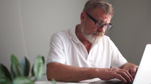 Ein Mann mit Bart, Brille und weißem T-Shirt macht sich Notizen in seinem Notizbuch und arbeitet mit einem Laptop. Geschäfts- und Rentnerkonzept