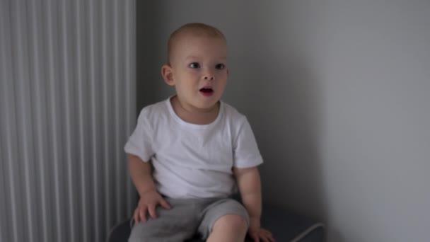 Das hübsche zweijährige Baby im weißen T-Shirt sitzt drinnen auf einem Stuhl vor grauem Hintergrund. Glückliche Kindheit