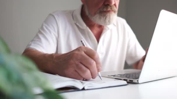 In Großaufnahme macht sich ein Mann mit Bart, Brille und weißem T-Shirt Notizen in seinem Notizbuch und arbeitet mit einem Laptop. Geschäfts- und Rentnerkonzept