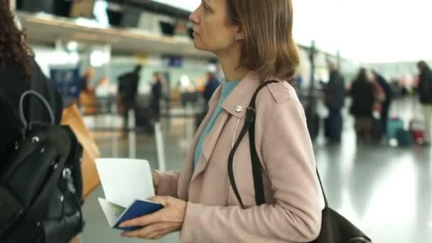 Dívka s letenkami na letišti se dívá na letový řád. Koncept cestování a služební cesty