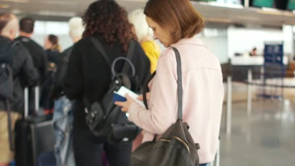 Girl with a backpack on her shoulder and a passport and tickets in her hands is standing in line at the reception. Meanwhile, a woman checks the tickets with the flight schedule