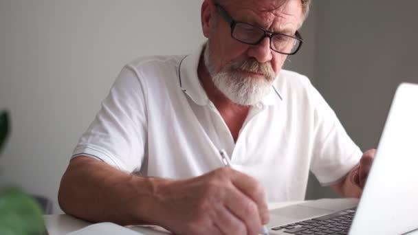 Reifer Mann und Computer. Opa mit Brille und grauem Bart beschäftigt neben dem Laptop, starrt auf den Bildschirm und tippt