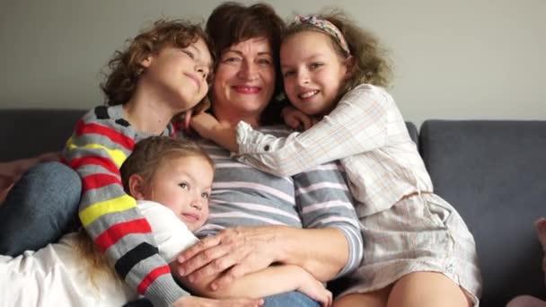 Babička a tři vnoučata sedí obejmutí na gauči. Happy family, Christmas party, Thanksgiving