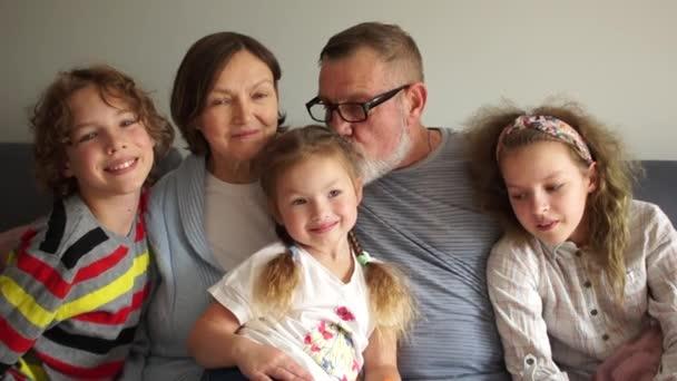 Blízký portrét velké šťastné rodiny. Prarodiče sedí na gauči a objímají svá tři vnoučata. Dědeček políbí vnučku na temeno hlavy