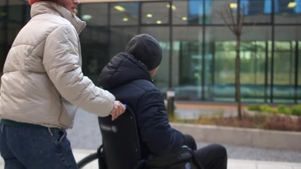 Eine junge Frau sitzt mit einem jungen Mann im Rollstuhl. Erholung nach einem Schlaganfall, Reha-Zentrum. zurück