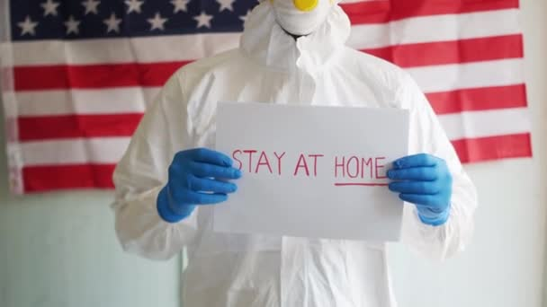 Covid-19 coronavirus epidemic in the USA, self-isolation and quarantine. Male doctor holding a sign in his hands with an appeal to stay at home