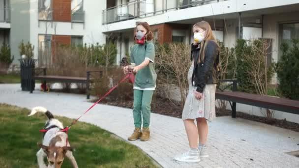 Ein Junge und ein Mädchen in Schutzmasken gehen während der Quarantäne mit ihrem Hund spazieren. Fürsorge für Tiere. Coronovirus-Epidemie, Covid-19-Virus
