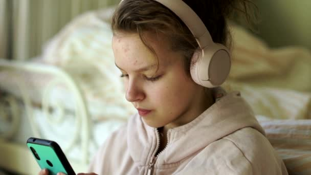 Girl schoolgirl in quarantine, self-isolation. Teen girl dries music, in the hands of a smartphone, looks up dreaming. Kids and Gadgets