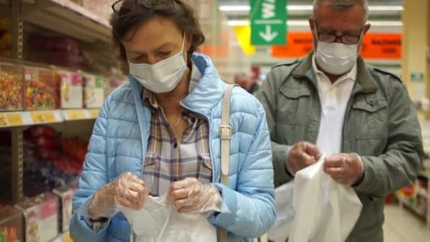 Mann und Frau in Masken und Handschuhen öffnen Plastiktüten. Schwierigkeiten beim Besuch eines Supermarktes während der Quarantäne von Coronavirus covid-19