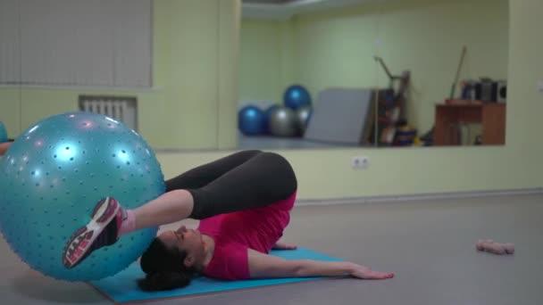 Frau trainiert die Bauchmuskulatur im Fitnessraum beim Heben von Gummibällen mit Füßen