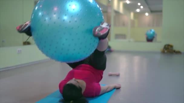 Frau im Fitnessstudio trainiert die Muskeln, die den Ball halten