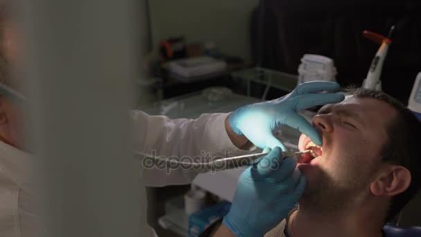 Close-Up, Zahnarzt Trocknung Hohlraum Wurzelkanal Luft unter Druck macht dann macht einer Inspektion des Wurzelkanals des Patienten mit Hilfe ein Spiegels