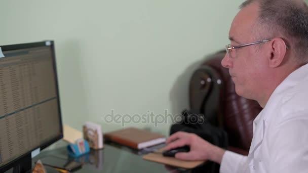 Zahnarzt findet eine Röntgenaufnahme des Patienten in der elektronischen Datenbank sitzen an einem Computer in der zahnärztlichen Praxis