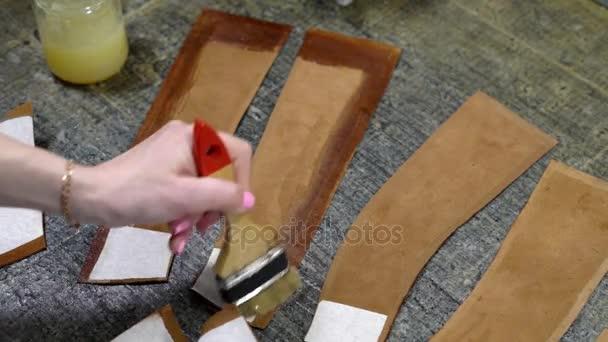 4e85514cb Mano de primer plano de una niña echa de menos pegamento los bordes de la  superficie interna de los detalles de cuero para hacer zapatos– metraje de  stock