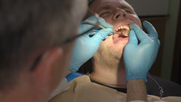Nahaufnahme der Zahnarzt mit einem Spiegel, das Ergebnis der Restaurierung der Zahn des Patienten zu überprüfen