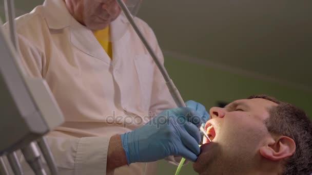 Zahnarzt-Ultraschall entfernt den Zahnbelag aus der Mundhöhle des Patienten