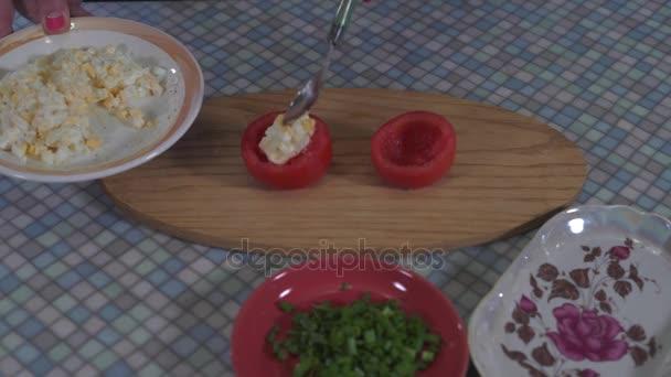 Detail z rukou mladá dívka s lžíci nacpat rajčata s jemně nasekané vařené vejce, oblečený s majonézou