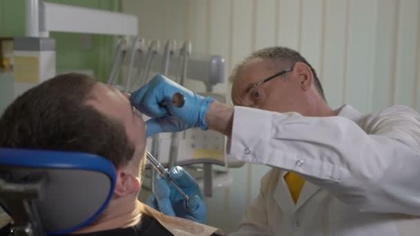 der Zahnarzt gibt eine Injektion der Narkose, der Patient sitzt auf dem Zahnarztstuhl