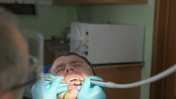 Zahnarzt in Schutzmaske trocknet den Luftstrom der zahnärztlichen Maschine den Hohlraum im Zahn des Patienten auf dem Zahnarztstuhl sitzen