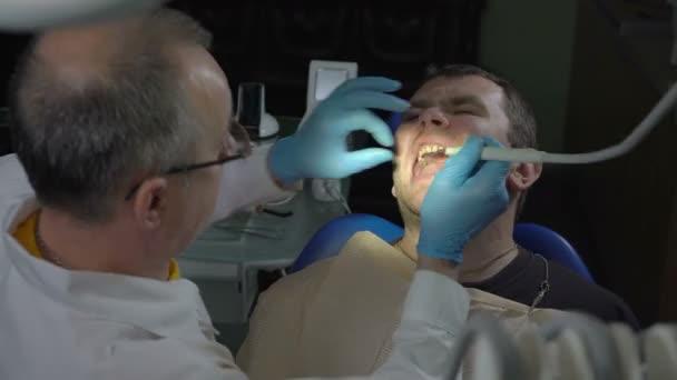Close-up Zahnarzt mit Hilfe von Ultraschall entfernt die Plaque aus der Mundhöhle des Patienten