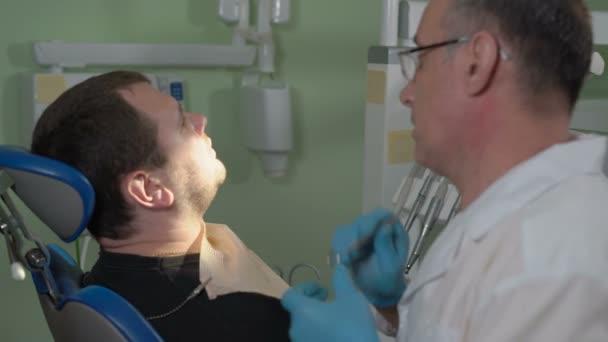 Zahnarzt mit einem Spiegel zu inspizieren die Mundhöhle des Patienten auf dem Zahnarztstuhl sitzen
