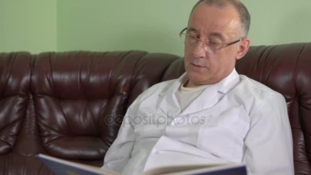 Zahnarzt lesen Dental Journal mit Illustrationen auf der Couch sitzen