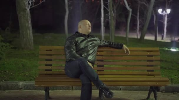Bald Man Pensively Looks Around The Night Sitting On A Park Bench In