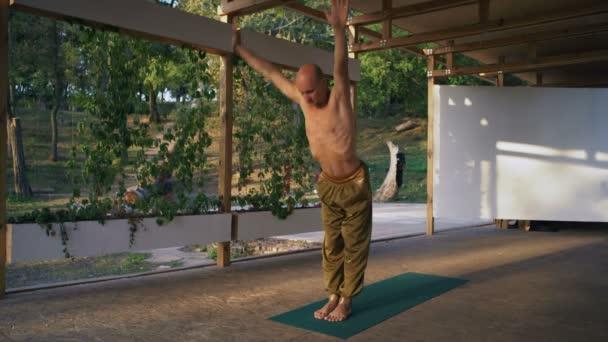 Giovane Yogi esegue asana inchinandosi al sole Suryanamaskar sul podio in legno nel parco cittadino