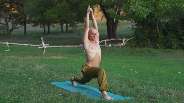 Mladý jogín s nahý trup praxe ásan jógy, provádí cvičení v městském parku časně ráno