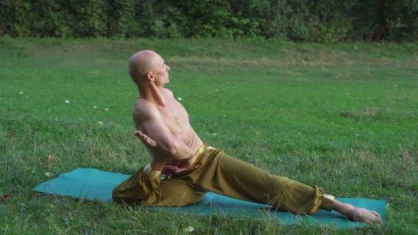 junger Yogi praktiziert Yoga-Asanas, führt morgens Übungen im Stadtpark durch