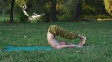 Bald Young Man Makes Gymnastics Yoga, Performs Asanas on Glade in the Forest