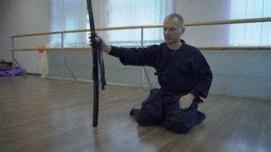 Seated on the Floor Samurai in Kimono Lies on Paul Katans Sword in Knives