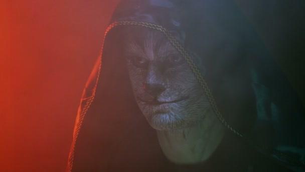 Detail, fešák v Chen Kapyushon s bestie bestie na tvář zamyšleně prohledá před sebe zakouřené tmavé Studio