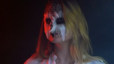 Close-up, Beautiful Girl with Owl Grim on Face Twirls Head in Parties Immune Bird in Smoky Dark Studio