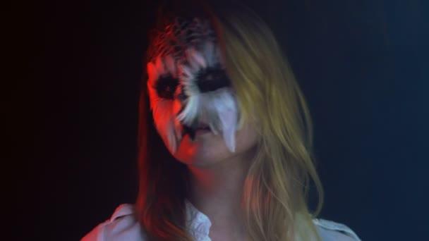 Close-up, bella ragazza con il gufo triste sul volto ghirigori testa in parti uccello immuni in Studio scuro fumoso